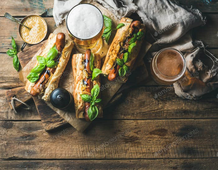Glasses of wheat unfiltered beer and homemade grilled sausage dogs