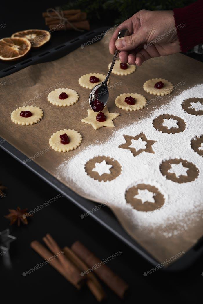 Hand applying marmalade on Christmas cookie