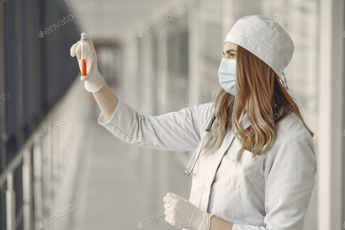 Woman in a mask and uniform holding a tube in her hands