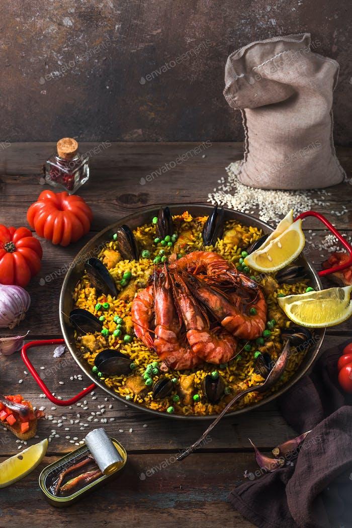 Traditionelle Paella mit Garnelen, Calamari und Muscheln in Paellara-Pfanne