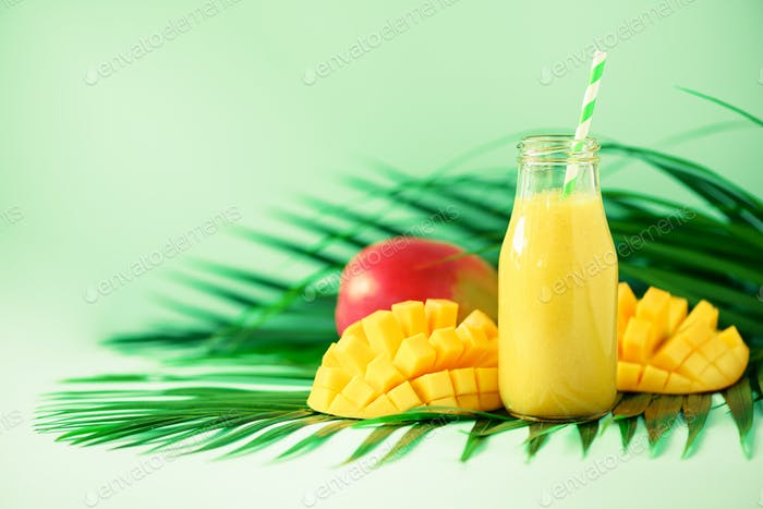 Delicious juicy smoothie with orange fruit and mango on turquoise background. Copy space. Pop art