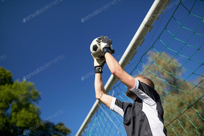 goalkeeper with ball at football goal on field