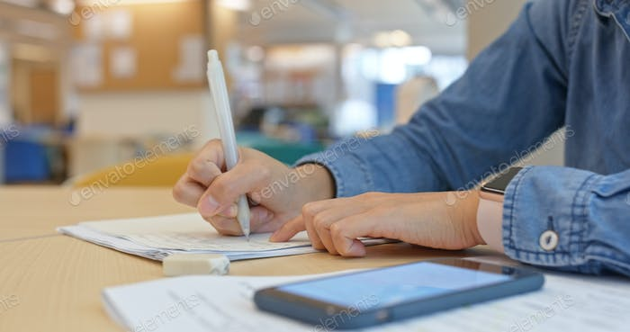 Woman do her paper with search on cellphone at school library