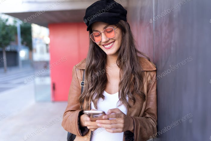 Pretty young woman using her mobile phone while standing in the street.