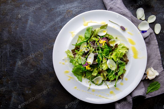 Lettuce arugula salad with edible flowers and microgreens on white plate, dark background