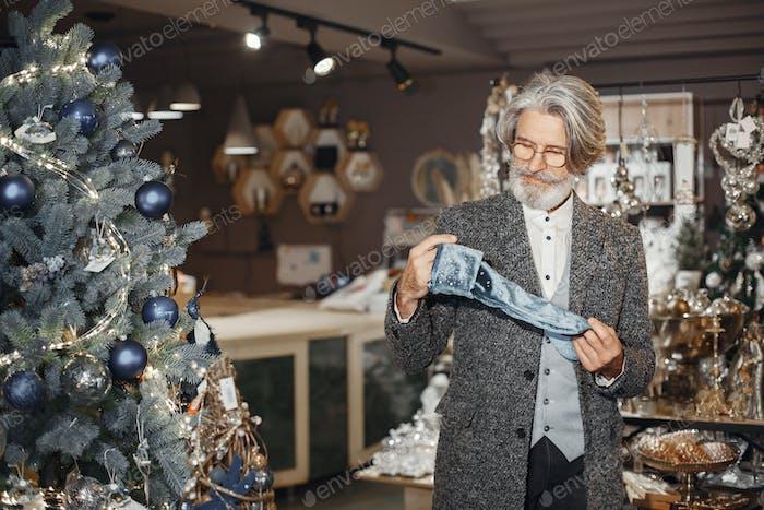 Senior man buying Christmas ornaments at store