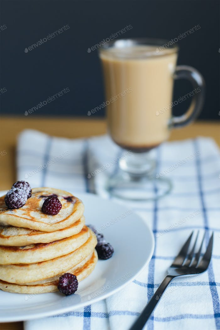 slapjack or oladyi with blackberry, frozen berries on plate, fork and coffee