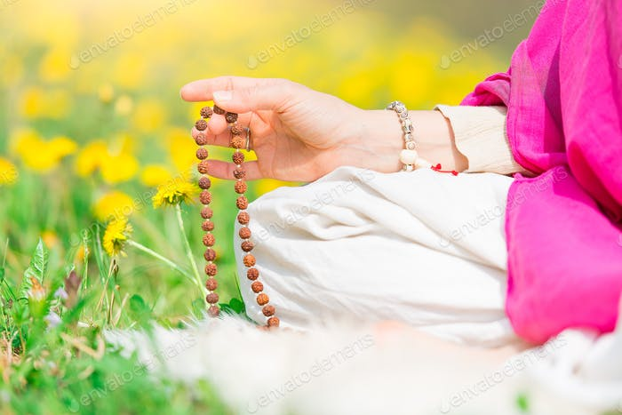 Woman reads the yoga mantra during practice with the mala