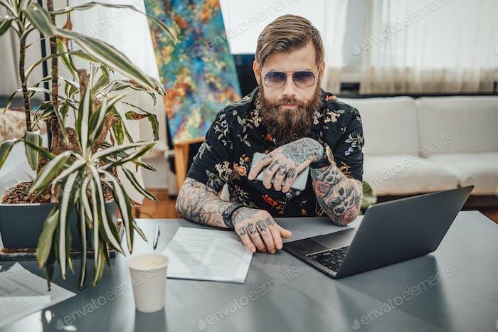 Hombre de negocios serio con gafas de sol y smartphone