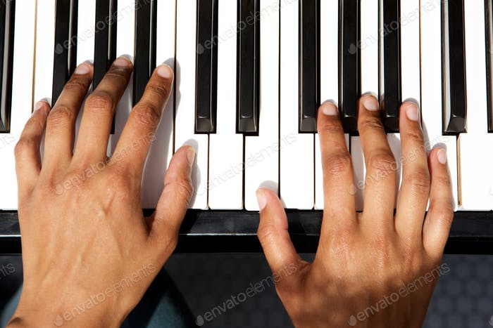 top view of female hands playing piano