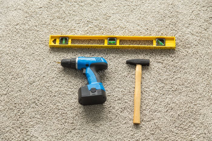 Construction concept - Hammer, drill and builders level on the floor, top view