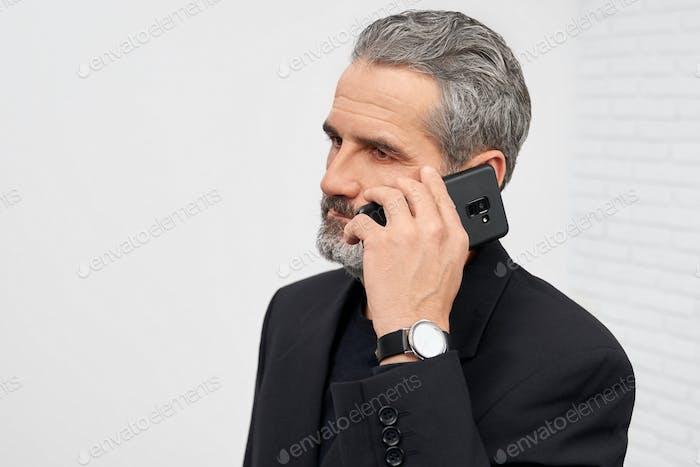 Бизнесмен в черном костюме разговаривает по телефону