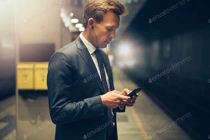 Young businessman standing on a subway platform reading text messages