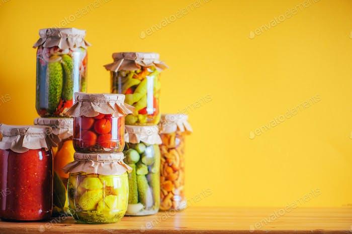 Konserviertes Gemüse in Gläsern auf orangefarbenem Hintergrund. Kopierraum. Gesundes fermentiertes Lebensmittelkonzept