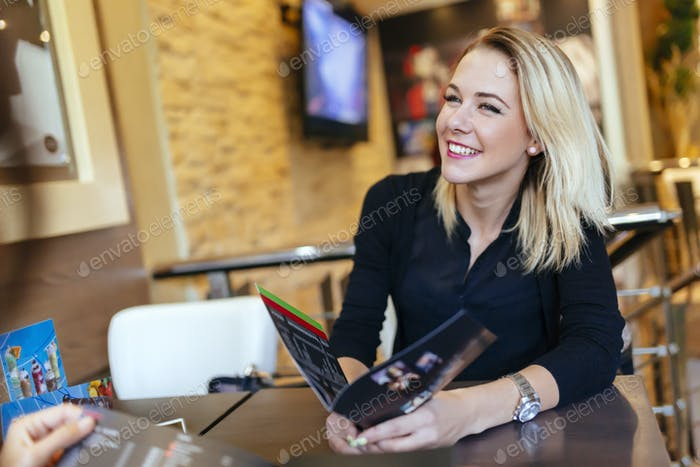 Happy woman in cafe holding menu