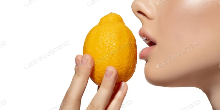 Freshness. Close up of beautiful young woman biting juicy lemon over white background. Cosmetics and