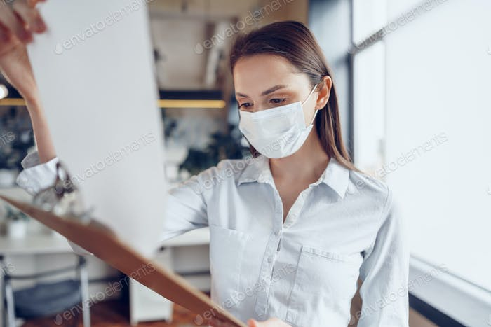 Young businesswoman in face mask standing in office and holding clipboard with documents