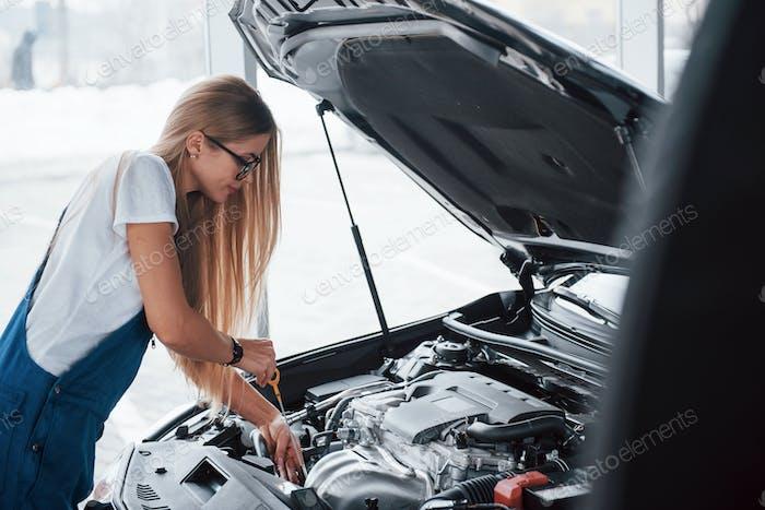 En el hermoso trabajo. Coche adicto mujer repara automóviles negro en el interior