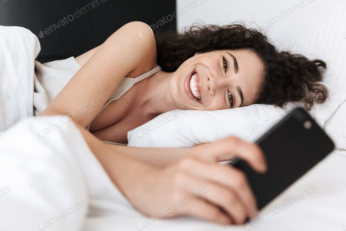 Image of happy caucasian woman 20s with dark curly hair lying in