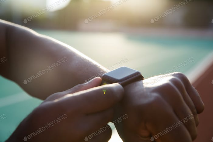 Close up of a young african sportsman adjusting smartwatch