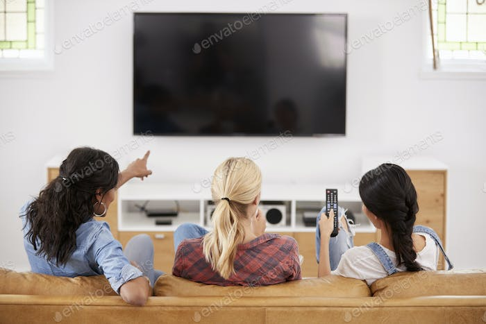 Rear View Of Female Friends Sitting On Sofa Watching Television