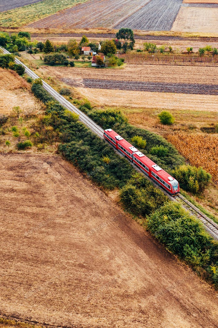 Red passenger train traveling through countryside, aerial view