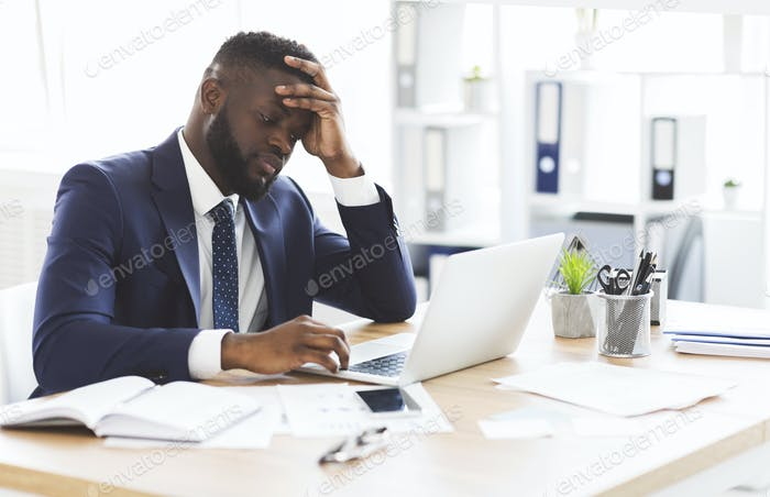 Exhausted young entrepreneur working with laptop in office