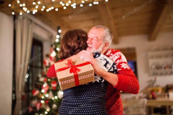 Seniorenpaar tauschen Geschenke zur Weihnachtszeit aus.