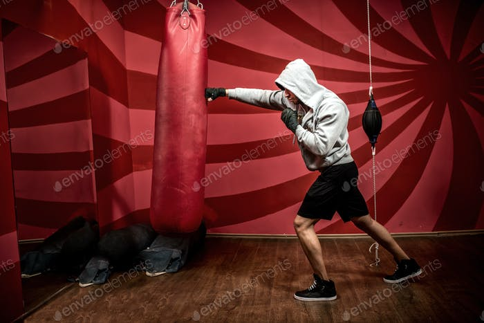 Athlete with hoody working out at boxing gym, getting ready for fight