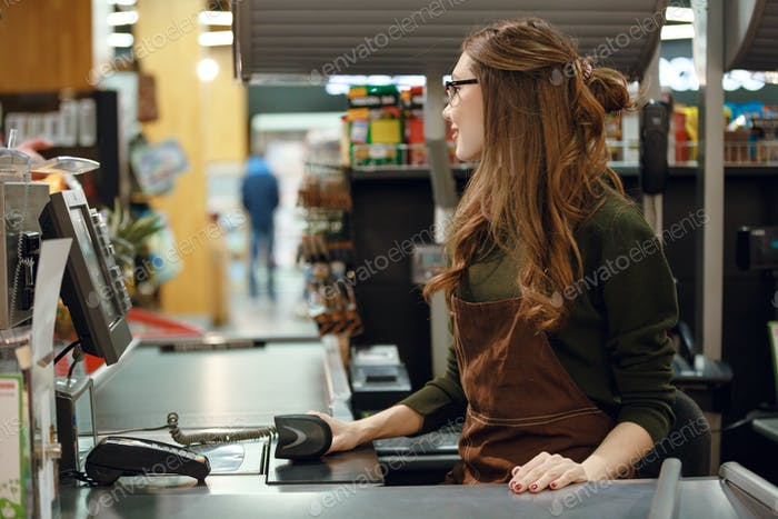Cashier woman on workspace in supermarket shop