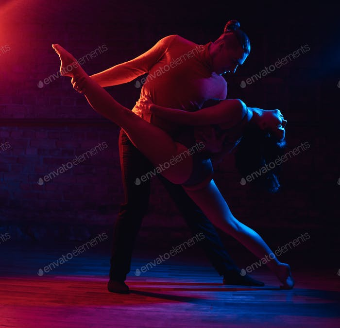 Beautiful couple dancing in a night club. Dancers performing in the dark with illumination