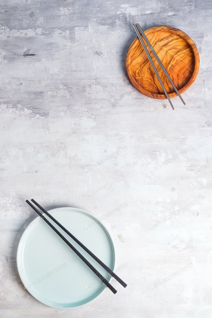 Rustic tableware, wooden bowls and ceramic plates with a copy space and chopsticks on stone