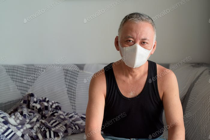Mature Japanese man with mask staying at home under quarantine