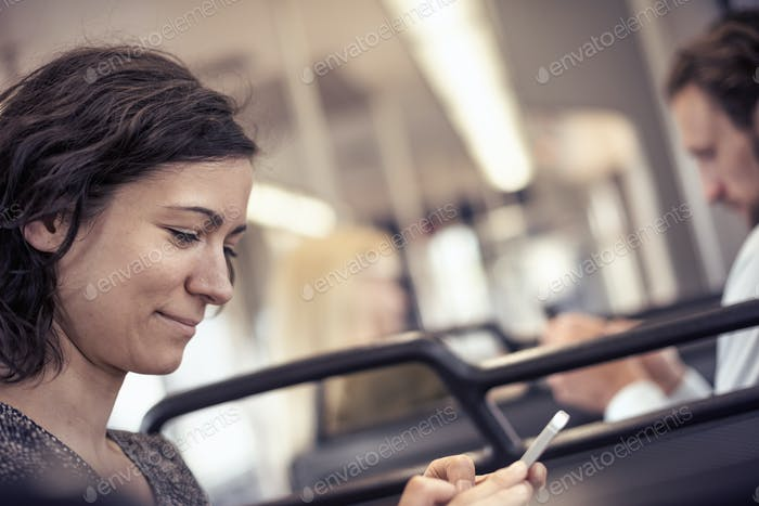 A woman on a bus looking down at her cell phone
