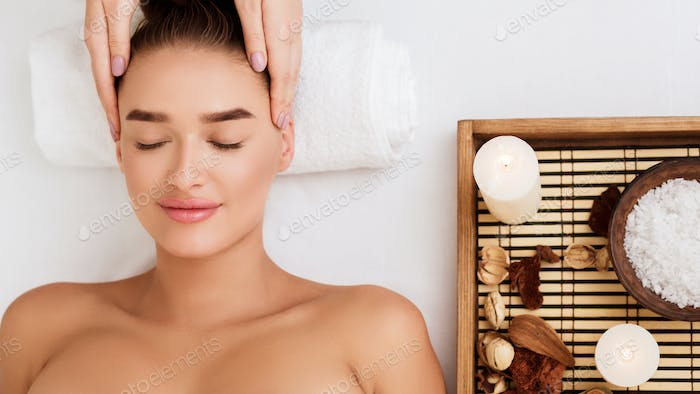 Young woman enjoying face massage and aroma therapy