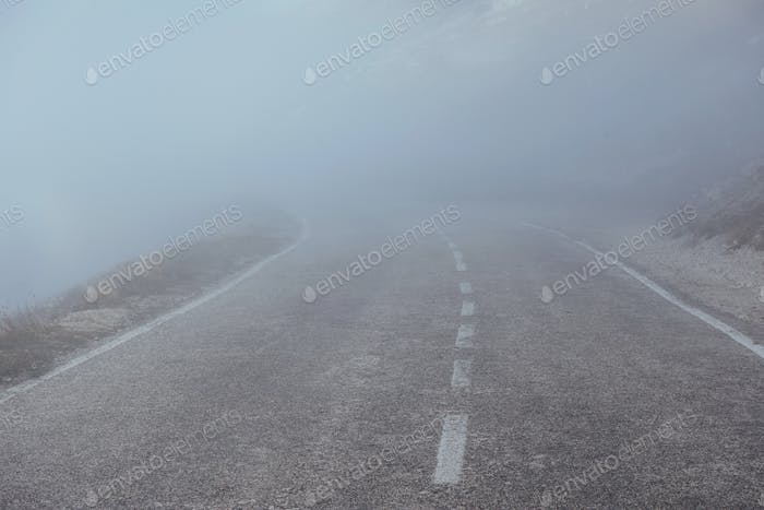 Mysterious looking road in the heavy fog near the mountains