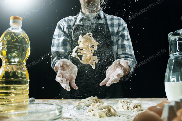 Professional male cook sprinkles dough with flour, preapares or bakes bread at kitchen table