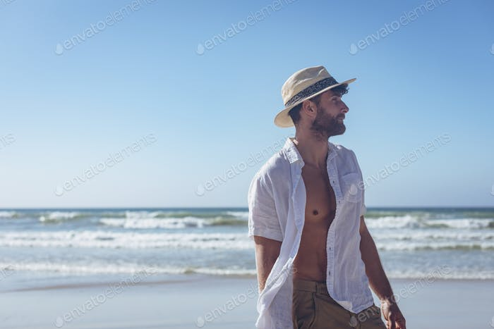 Side view of handsome young Caucasian man standing at beach. He is relaxed
