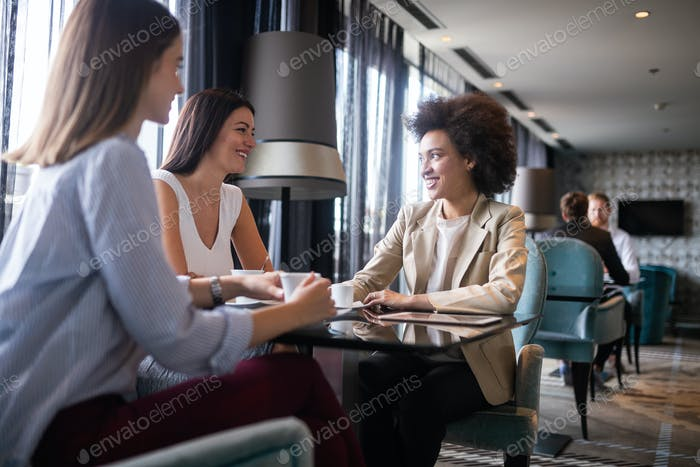Group of young happy women drinking coffee