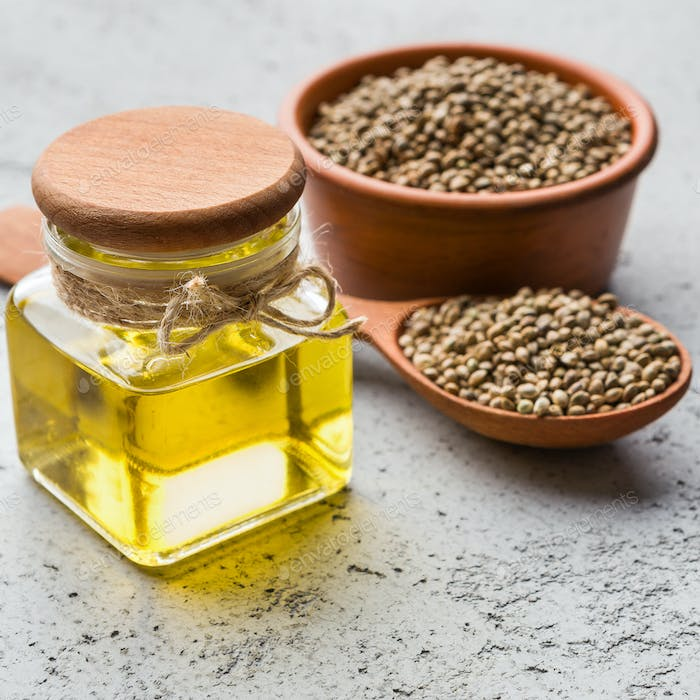 Hemp oil and hemp seeds on concrete background