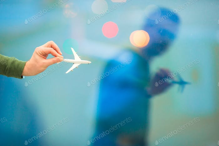 Closeup hand holding an airplane model toy at the airport background big window
