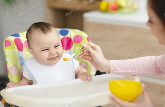 Cheerful baby eating in kitchen in high chair