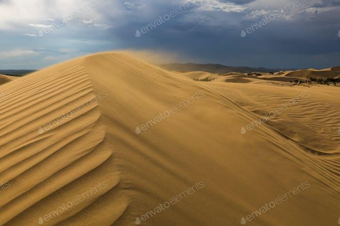 Sturmwolken über Sanddünen in der Wüste