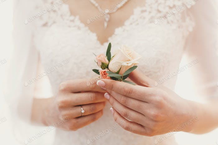 Beautiful bride holding stylish simple boutonniere in hands