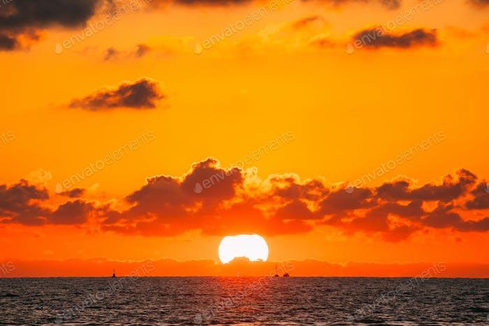 Sundown Over Sea Horizon At Sunset. Natural Sunrise Sky Warm Col
