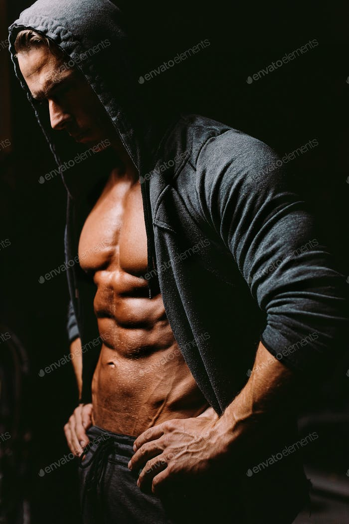 Brutal bodybuilder athlete torso in hoodie with abs and chest naked