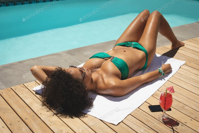 Rear view of young African American woman relaxing at poolside in her backyard on a sunny day
