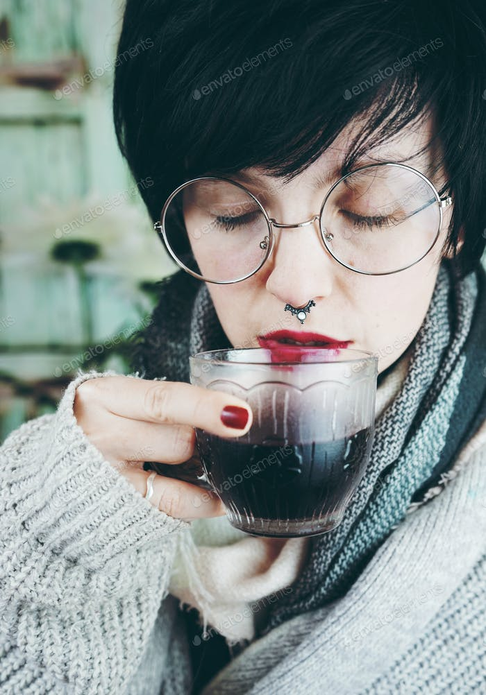 Young woman drinking a cup of cold coffee