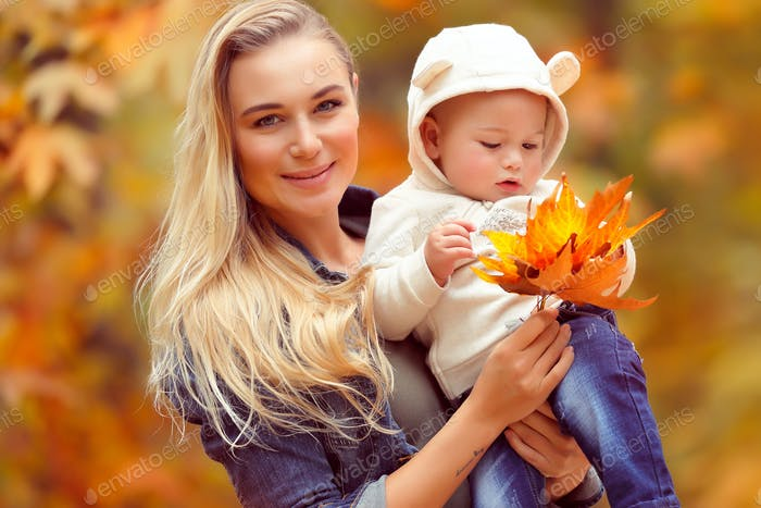 Happy mother with baby in autumn park