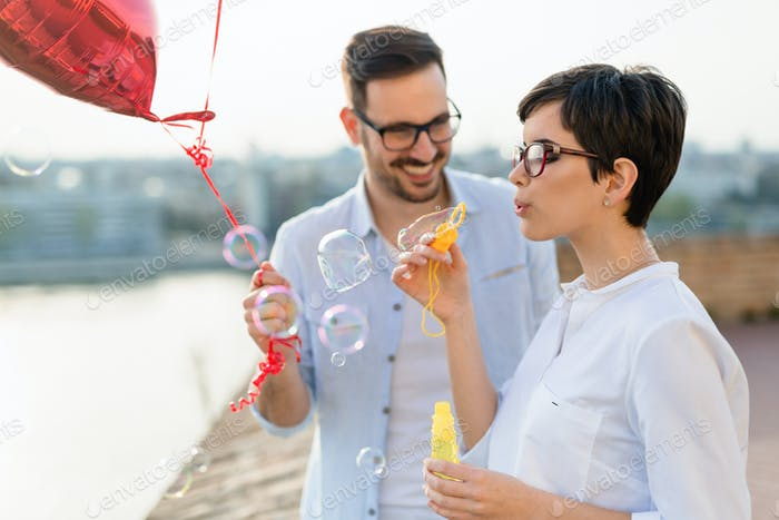 Happy couple dating and smiling while blowing bubbles